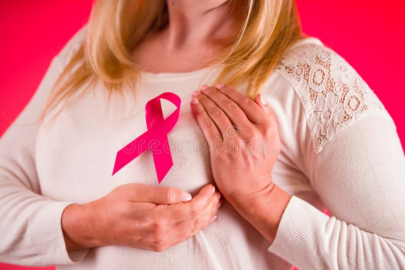 Close up of a woman wearing a white blouse with pink breast cancer awareness ribbon, healthcare and medicine concept in stock photography