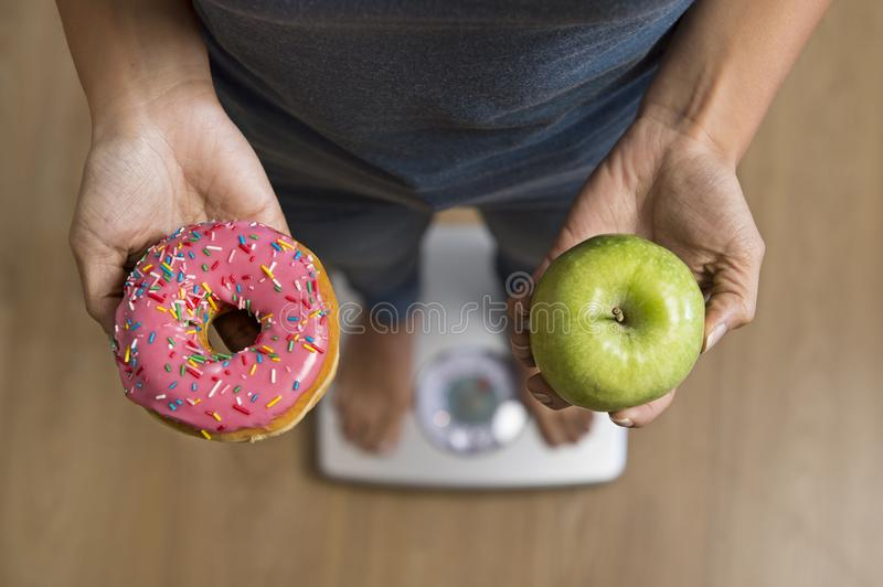 Close up woman on weight scale holding in her hand apple fruit and donut as choice of healthy versus unhealthy food stock photography