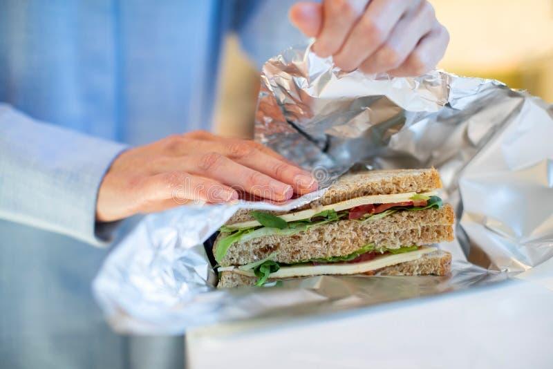 Close Up Of Woman Wrapping Sandwich In Non Reusable Aluminium Foil stock photos