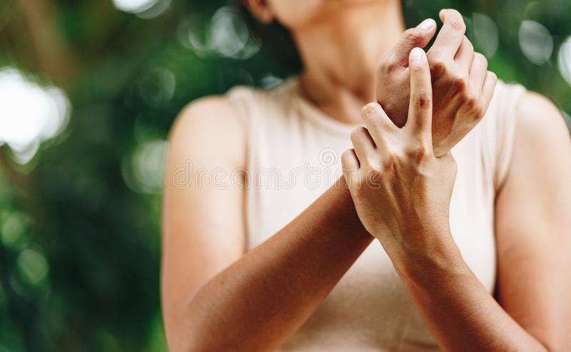 Close up Woman wrist pain. Health care concept. Close up woman holding her wrist symptomatic Office Syndrome. Pain in the joints of the hands. Carpal tunnel royalty free stock images