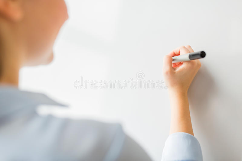Close up of woman writing something on white board. Office, business, people and education concept - close up of woman with marker writing or drawing something stock images