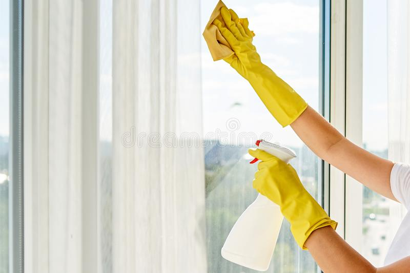 Close up of woman in yellow rubber gloves cleaning window with cleanser spray and yellow rag at home or office, copy space. Close up of woman in yellow rubber royalty free stock photos