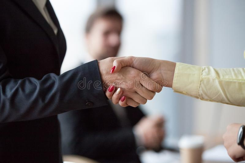 Close up of womans handshake in office royalty free stock photo