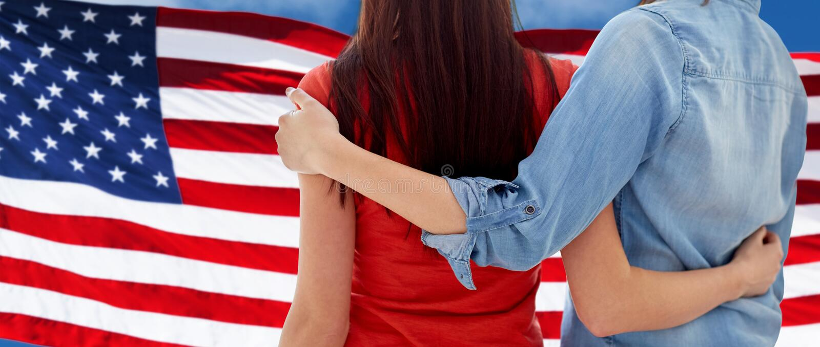 Close up of women couple over american flag. People, homosexuality, same-sex marriage, gay and love concept - close up of happy women couple hugging over stock image