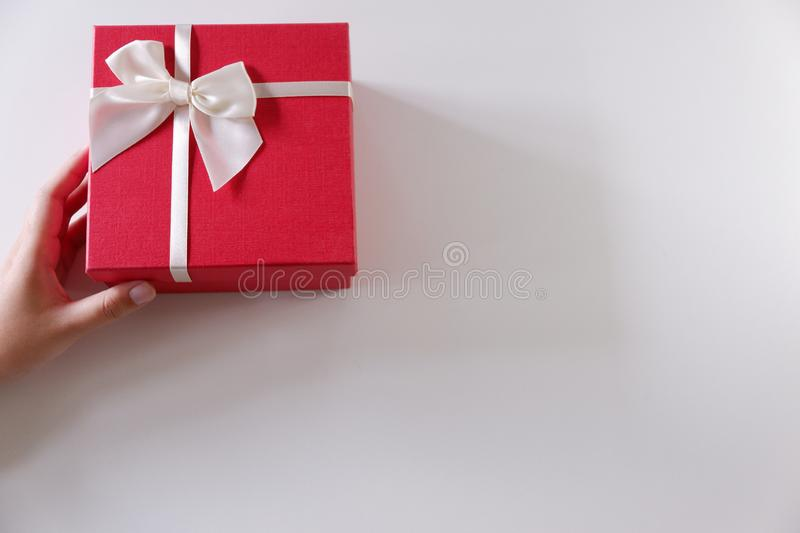 Close-up women hands sending red gift box with white ribbon on white background.  royalty free stock image