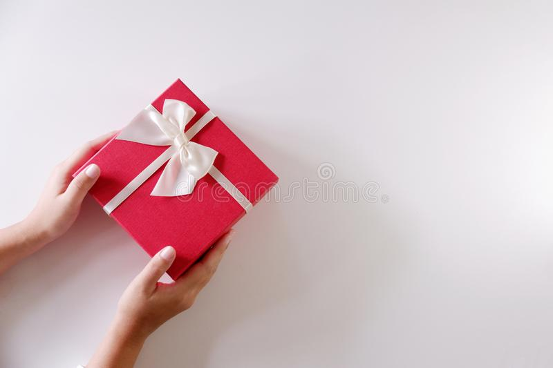 Close-up women hands sending red gift box with white ribbon on white background.  stock photography