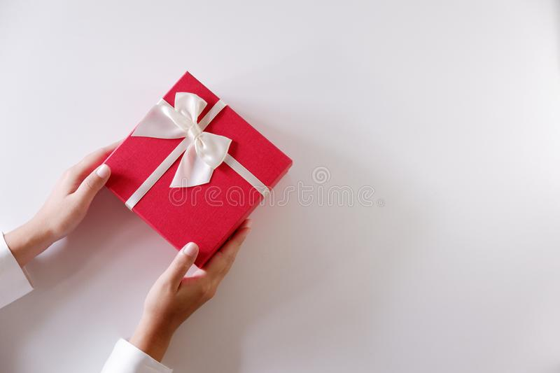 Close-up women hands sending red gift box with white ribbon on white background.  stock image