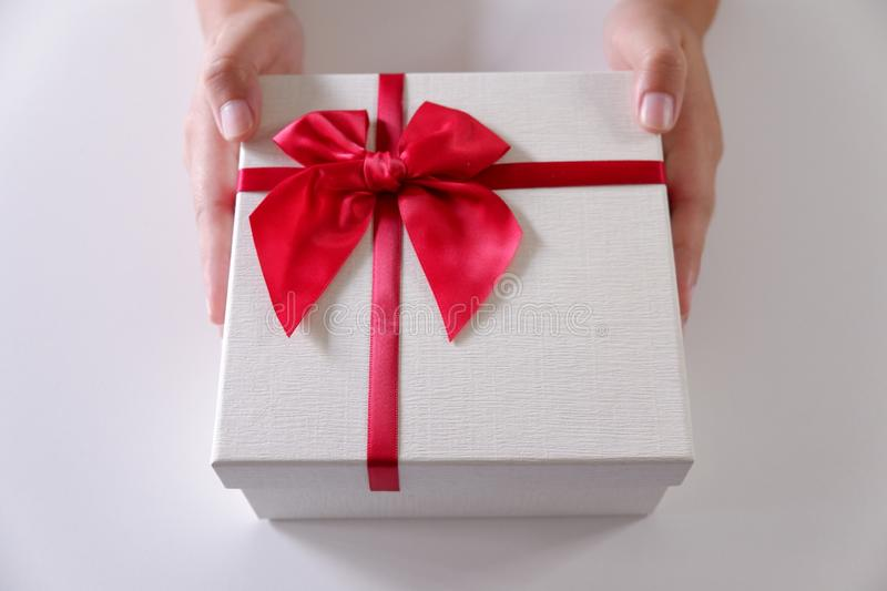 Close-up women hands sending white gift box with red ribbon on white background. Close-up women hands sending white gift box with red ribbon on white background stock images