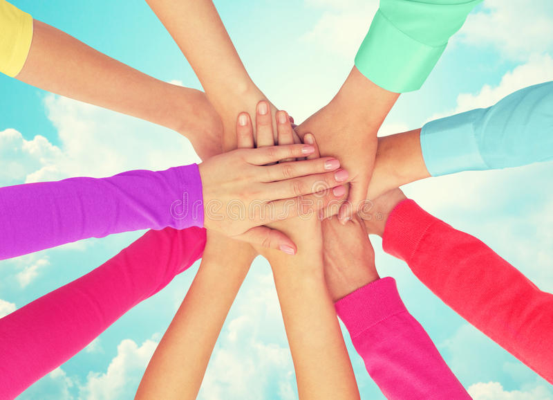 Close up of women hands on top in rainbow clothes. People, gesture, gay pride and homosexual concept - close up of women hands in rainbow clothes on top of each stock image