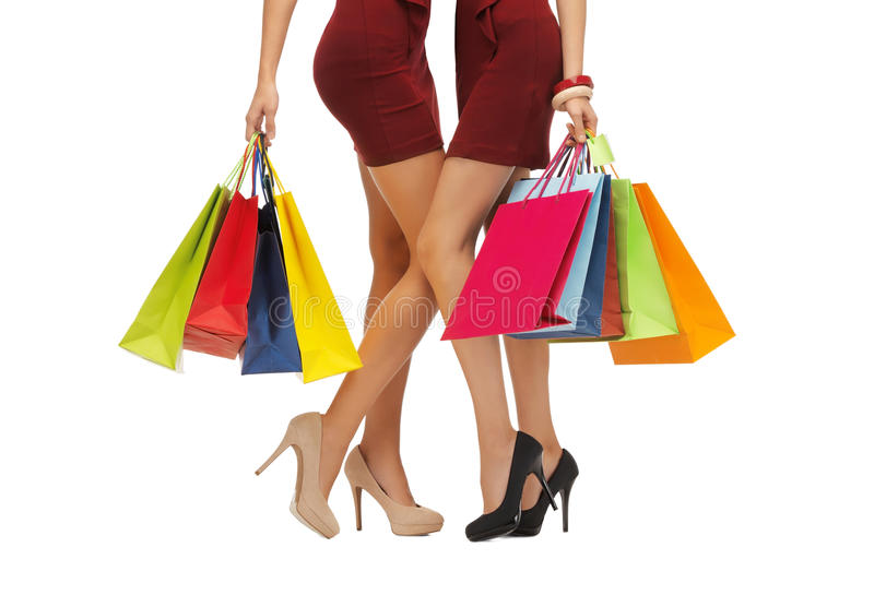 Close up of women on high heels with shopping bags. People, sale and discount concept - close up of women in red short skirts and high heeled shoes with shopping royalty free stock photos