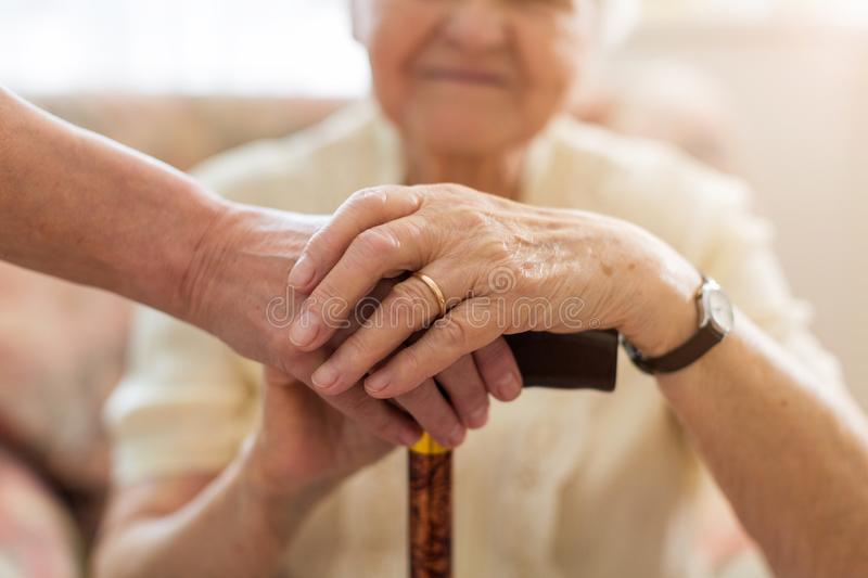 Woman holding senior`s hands leaning on walking cane stock photography