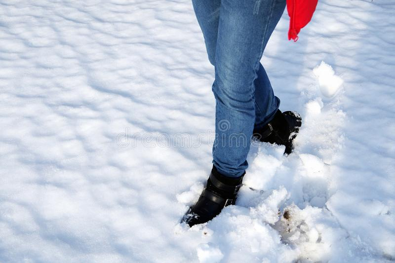 Close-up of women legs against white snow. Close-up of women legs in blue jeans and black boots against white snow stock photos