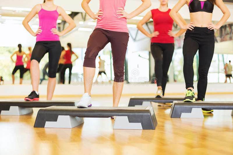 Close up of women legs steping on step platform. Fitness, sport, training, gym and lifestyle concept - close up of women legs steping on step platform in gym stock photo