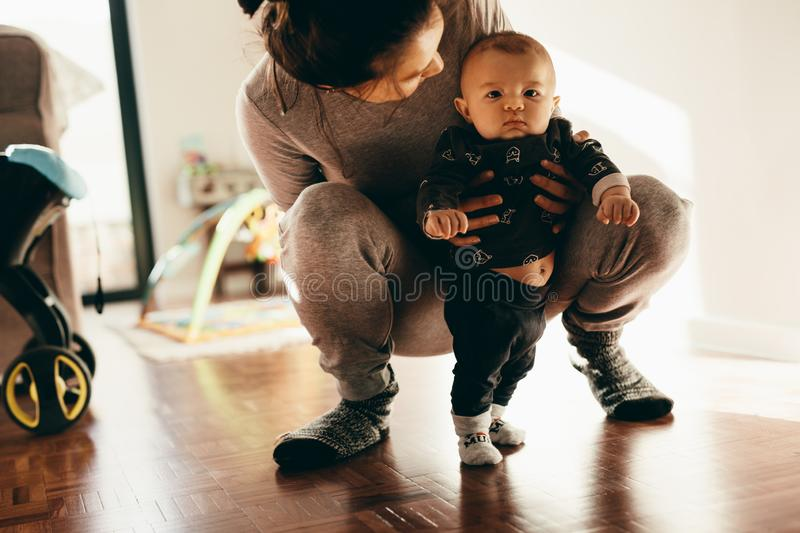 Woman holding her baby squatting on floor. Close up of a women playing with her baby squatting on the floor and holding him. Mother making her baby stand on stock image