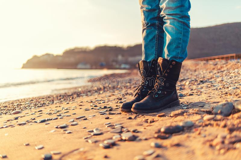 Close-up of women`s feet in black casual shoes, standing on the sand of the beach, autumn or winter. Copy space royalty free stock image