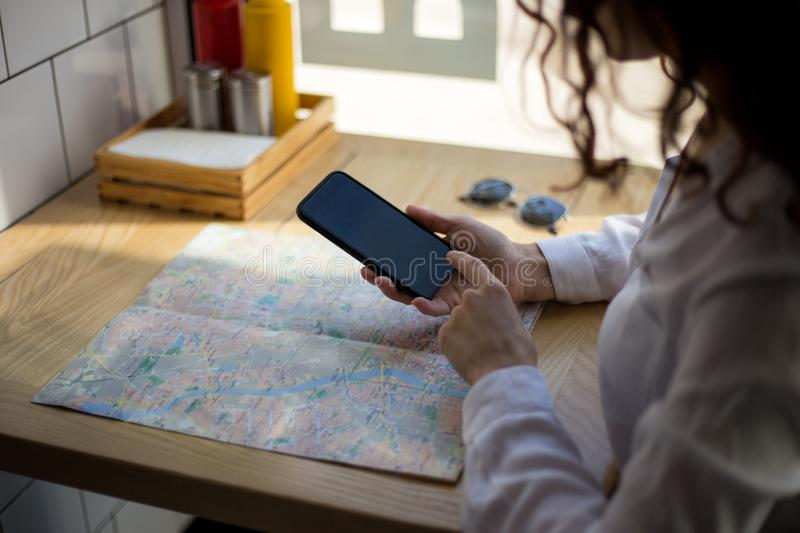 Close up of women`s hands holding cell telephone, uses mobile phone in cafe, above of map. royalty free stock photography