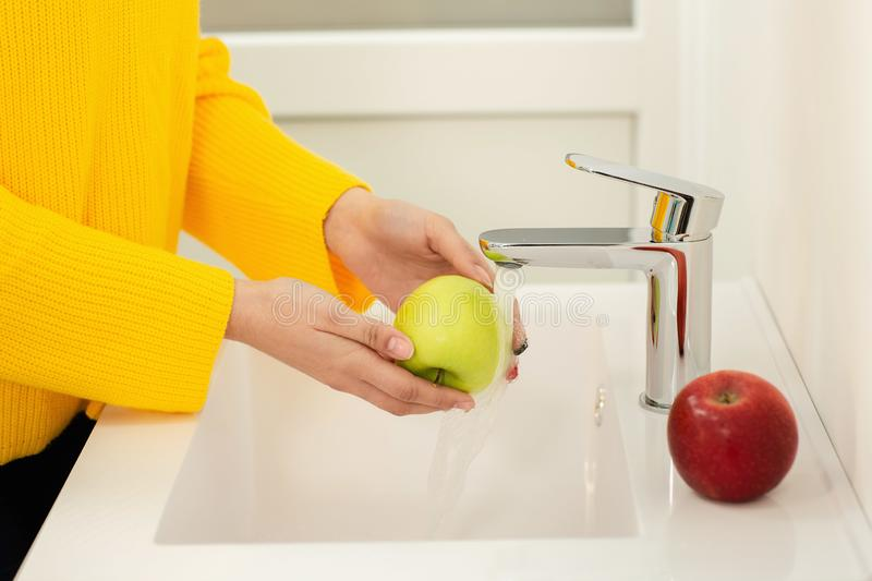 Close up of women`s hands washing green apple in sink stock photos