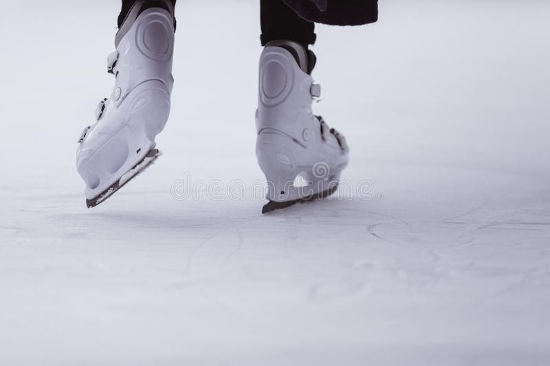 close-up of womens legs on skates in winter on an open skating rink, place for text royalty free stock image