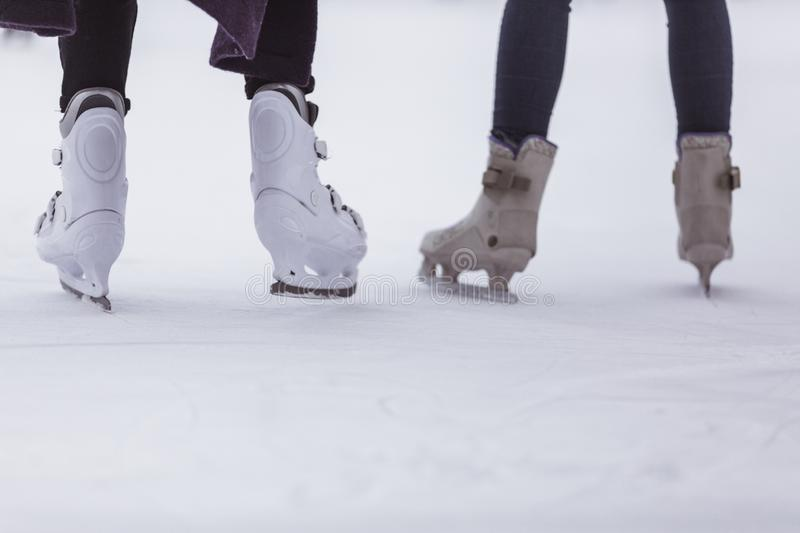 close-up of womens legs on skates in winter on an open skating rink, place for text stock image