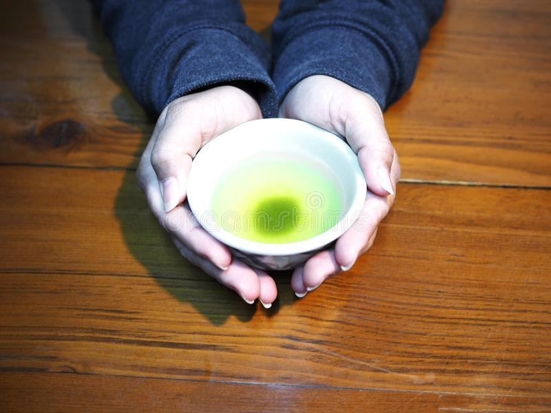 Close up wonan hand holding white cup of hot  Japanese green tea stock image