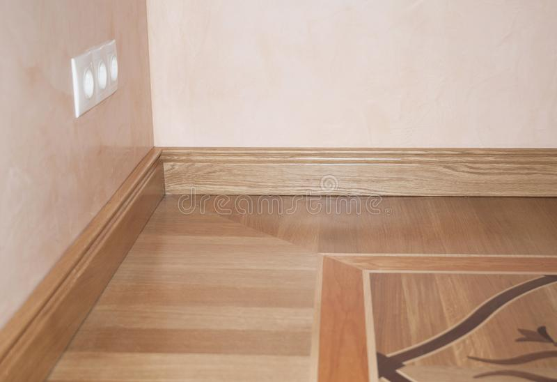 Wood Flooring. Skirting Board Oak Wooden Floor . Flooring with Wooden Batten Repair. CLose up on Wood Flooring. Skirting Board Oak Wooden Floor stock image