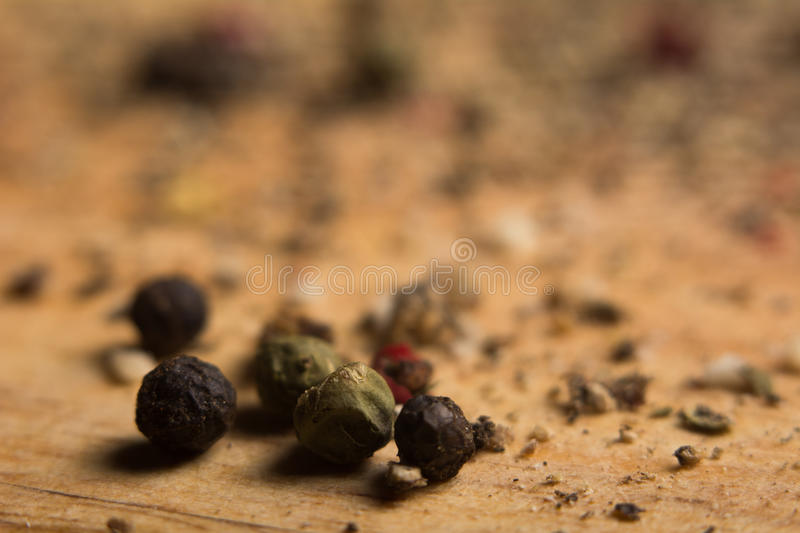Close-up on a wooden board, ground pepper and peas. Wooden background with black, green and red bell pepper royalty free stock photo