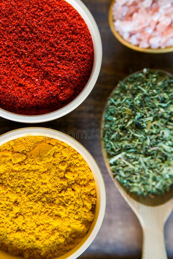 Various colorful herbs and spices on wooden table royalty free stock images