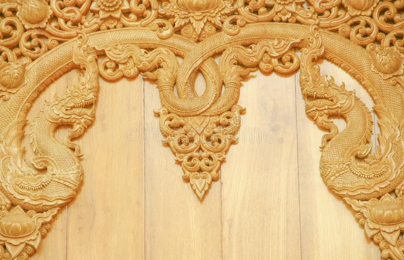 Wooden carving with two naga patterns on wall in temple stock photography