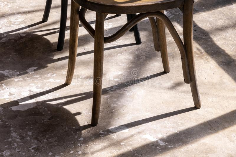 Close up wooden chair legs with shadow and light on grunge cement ground royalty free stock images