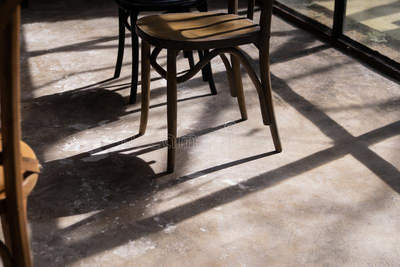 Close up wooden chair legs with shadow and light on grunge cement ground stock photo