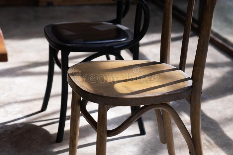 Close up wooden chair seat with shadow and light on grunge cement ground royalty free stock photo