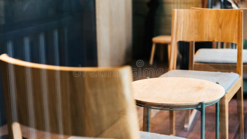 Close-up wooden chairs and empty low table inside cafe. Warm and cozy atmosphere.  stock photography