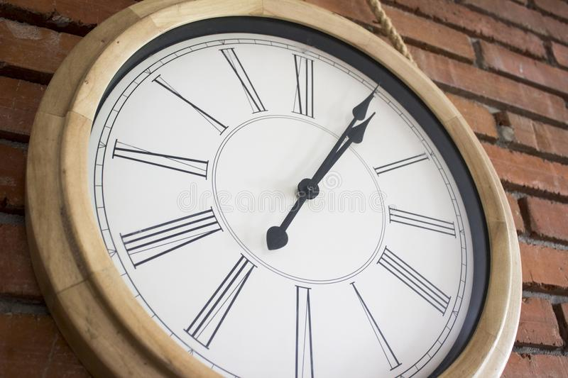Close–up of a wooden wall clock with roman numerals hanging in a red brick wall. royalty free stock images