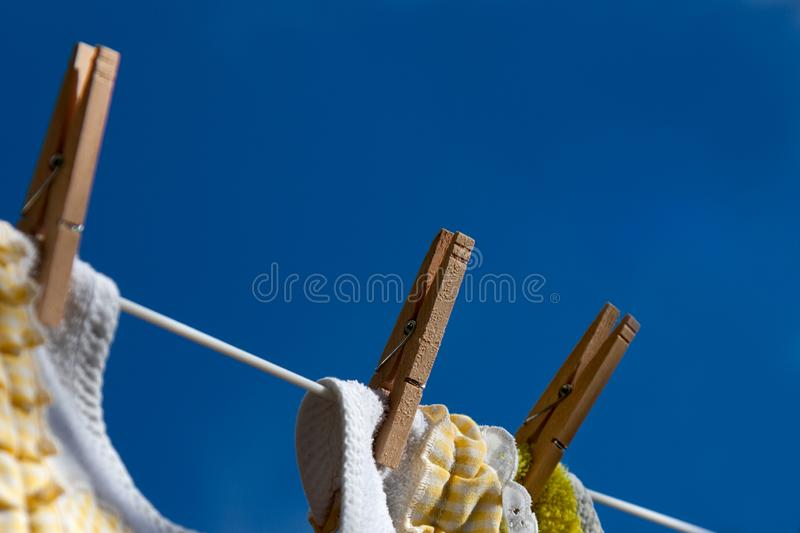 Close-Up of Wooden Clothespins Holding Clothes on Clothesline royalty free stock photography
