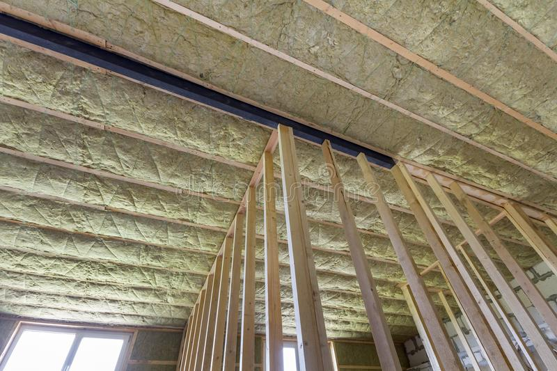 Close-up of wooden frame for future walls and ceiling insulated. With rock wool and fiberglass insulation staff for cold barrier. Comfortable warm home, economy stock image