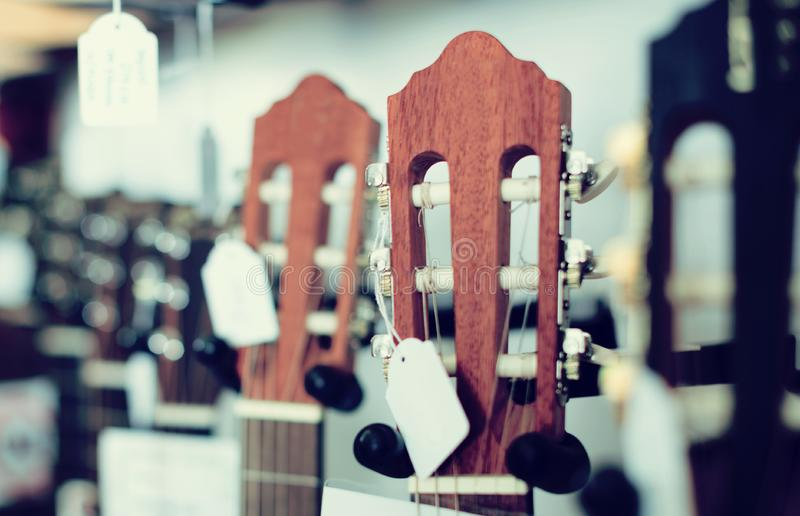 Close-up of wooden fretboard of guitar. Close-up of wooden head of guitar in music shop stock photo
