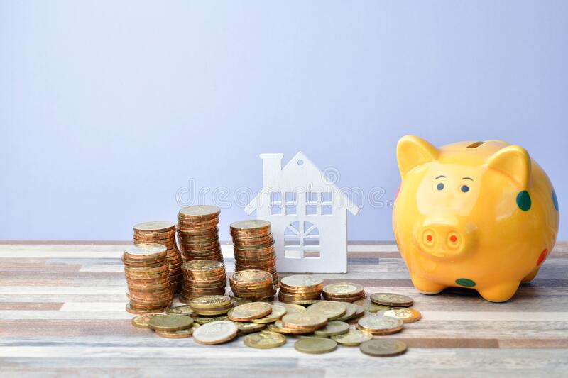 Close up of Wooden home, piggy bank and stack of money coins stock photography