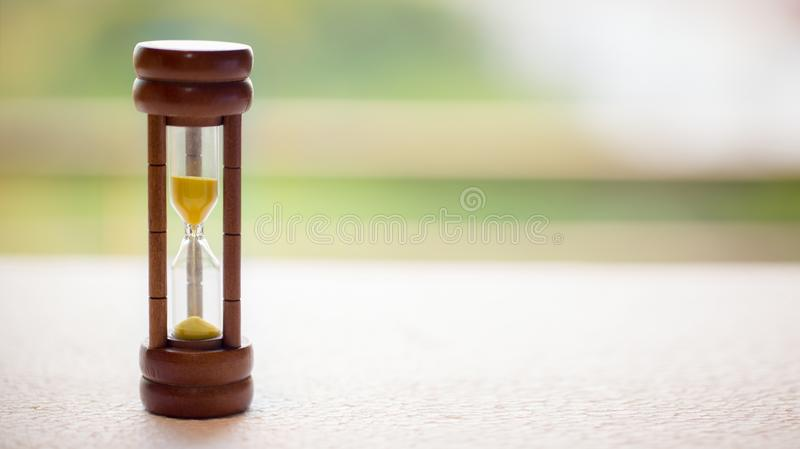 Close up wooden hourglass on table with motion blur background stock photo