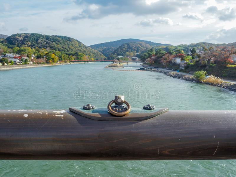 Close up wooden rail with metal plate on bridge with beautiful river on sky with cloud background. Uji, Japan stock image