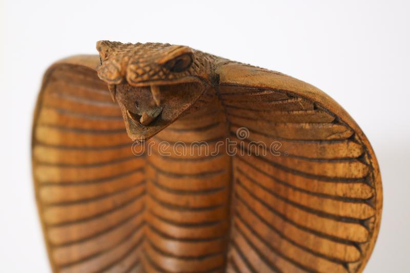 Wooden statuette of a cobra, white background. Close-up a wooden statuette of a cobra, white background, collectibles stock image