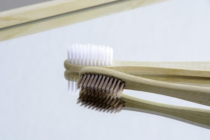 Wooden white and brown toothbrushes on mirror. stock images