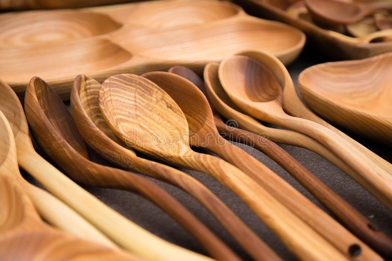Close up of wooden utensils for the kitchen, bowls, spoons on dark background. Concept of natural dishes, a healthy lifestyle. stock image