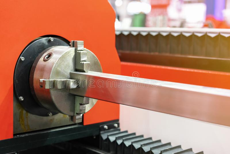 Close up work piece metal square pipe during clamp by multipurpose auto chuck rotate set for high precision automatic laser. Cutting machine or other stock image