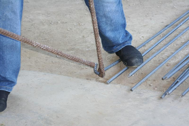 Worker bending steel with steel bending equipment by hand. Close up Worker bending steel with steel bending equipment by hand royalty free stock photos