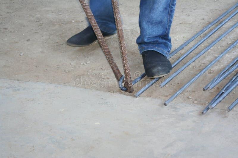 Worker bending steel with steel bending equipment by hand. Close up Worker bending steel with steel bending equipment by hand stock images