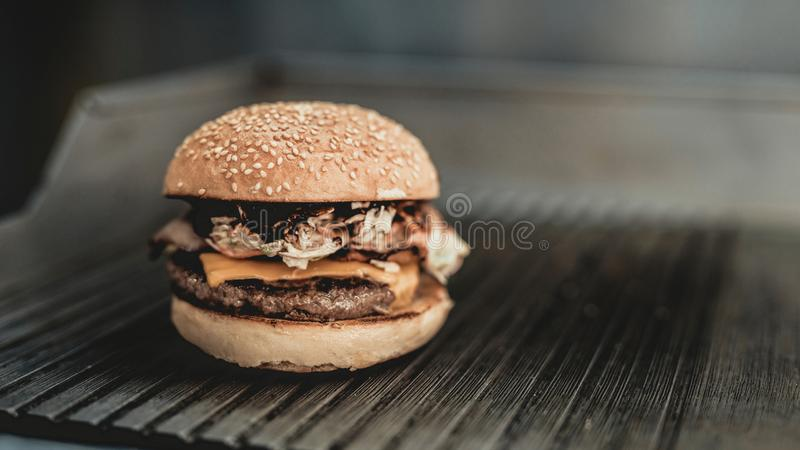 Close up. Worker Cooking Burger in Food Truck. Street Food Concept. Food in Town. Selling Snacks. Preparation of Sandwich. Unhealthy Food. Hands in Gloves royalty free stock photography