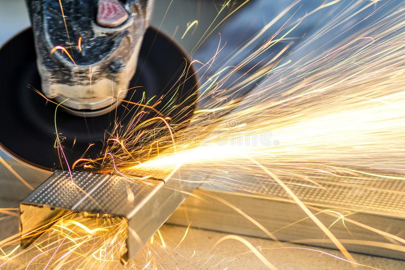 Close-up of worker cutting metal with grinder. Sparks while grin stock images