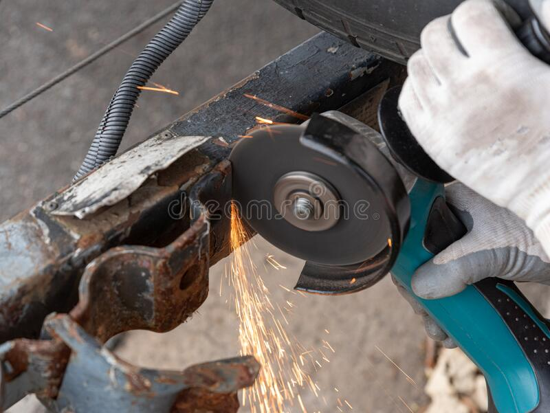 Close up of a worker grinding off a piece of metal from a hitch stock photo