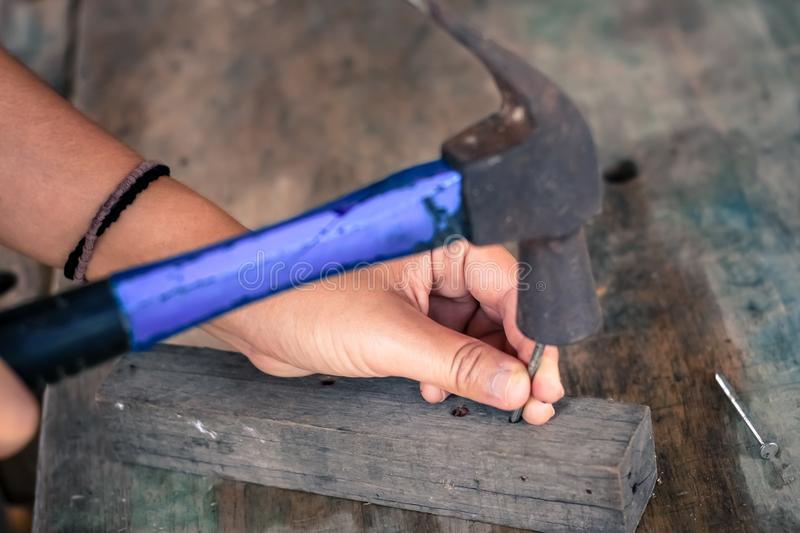 Close up worker hammering nail into wood, vintage style stock image