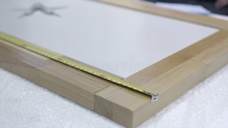 Close-up of worker measures wooden frame. Action. Control measurement of wooden frame. Worker of furniture factory royalty free stock photography